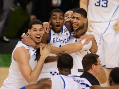 Wildcats forwards Eloy Vargas (left), Michael Kidd-Gilchrist (center) and Anthony Davis (right) celebrate after defeating the Kansas Jayhawks 67-59 in the national championship game.