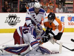 Flyers forward Zac Rinaldo tries to punch the puck in while Rangers goalie Henrik Lundqvist attempts to cover it up during their game on Tuesday.