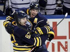 The Sabres' Derek Roy celebrates his game-winning goal in overtime by jumping into teammate Marcus Foligno's arms after their game against the Maple Leafs on Tuesday.