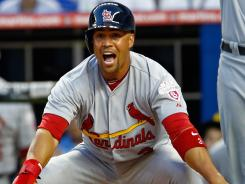 The Cardinals' Carlos Beltran motions to slide during Opening Day against the Miami Marlins at Marlins Park.