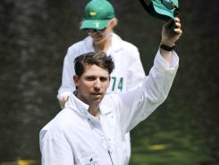 NASCAR driver Denny Hamlin waves to the crowd at the ninth green at Augusta National, where he was caddying for Bubba Watson in the Par 3 Contest. Hamlin just missed a 20-footer for birdie when Watson let him putt.