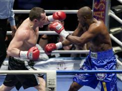 Russia's Denis Lebedev, left, earned his third straight victory in Moscow after knocking out contender Shawn Cox, of Barbados, in the second round.