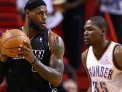 Miami forward LeBron James, left, posts up on Oklahoma City forward Kevin Durant in the first quarter at the American Airlines.