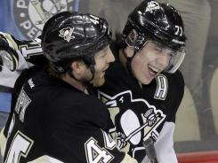 Pittsburgh Penguins' Evgeni Malkin (71) celebrates his 49th goal of the season with teammate Brooks Orpik. The Penguins beat the New York Rangers 5-2 and snagged a playoff berth.