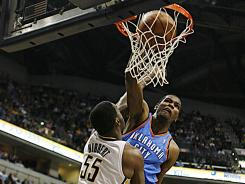 Thunder forward Kevin Durant dunks two of his 44 points over Pacers center Roy Hibbert during the first half of their game Friday. Despite Durant's big game, Hibbert's Pacers came away with the victory.