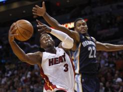 Heat guard Dwyane Wade rises up to the hoop while Grizzlies guard Rudy Gay tries to stop him during their Friday night matchup. Gay and the Grizzlies came out victorious.