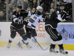 Los Angeles center Jarret Stoll (28) and defenseman Drew Doughty (8) react just after San Jose's Ryane Clowe put his stick onto the ice from the bench and poked the puck away from Stoll.