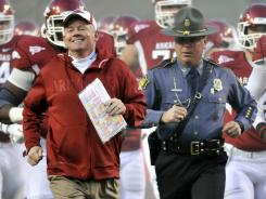 Arkansas football coach Bobby Petrino, left, is followed by Arkansas State Police Captain Lance King before a football game in 2011. King is the police officer that drove Petrino to the hospital after his motorcycle crash this week.