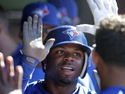 Toronto Blue Jays' Rajai Davis is congratulated in the dugout after scoring on a single by teammate Colby Rasmus in the 12th inning the Blue Jays' 7-4 win over the Cleveland Indians on Saturday.