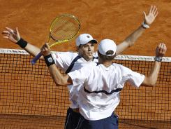 Mike, back, and Bob Bryan react after winning their doubles match to give the U.S. a 2-1 lead over France in their Davis Cup quarterfinal.