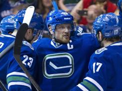Vancouver's Henrik Sedin, middle, celebrates with after scoring a power play goal in the Canucks' 3-0 win over the Edmonton Oilers on Saturday night.