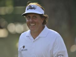 Phil Mickelson flashes a smile walking down 17th fairway on his way to a third-round 66 to take to 9 under, one shot out of the lead.