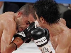Champion Shinsuke Yamanaka, right, lands a right to the nose of Vic Darchinyan during the eighth round of their 12-round scheduled WBC bantamweight title bout in Tokyo on Friday. Yamanaka scored a unanimous decision.