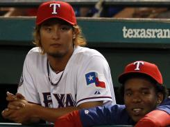 Yu Darvish, observing Saturday's game from the dugout with teammate Neftali Feliz, right, will make his major league debut tonight. The Rangers won an offseason bidding competition for the Japanese star.