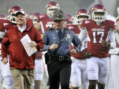 Arkansas State Police Capt. Lance King, right, has provided pregame and game day security to Razorbacks football coach Bobby Petrino for the last two years. King drove Petrino to a hospital after his April 1 motorcycle crash