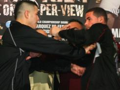 Brandon Rios, left, and Richard Abril get into a shoving match during a press conference Monday in Los Angeles.
