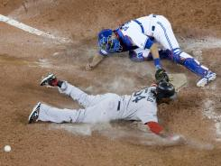Red Sox outfielder Darnell McDonald slides into home plate to score against Blue Jays catcher J.P Arencibia during the ninth inning of their Monday night game, whicc Boston won 4-2.