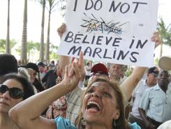 Protestor Olga Gomez gestures outside Marlins Stadium as throngs gathered to demand further discipline for manager Ozzie Guillen.