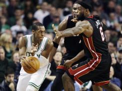 Celtics guard Rajon Rondo passes under pressure from Heat forwards LeBron James and Chris Bosh in the first half of their Tuesday game. Rondo had a triple-double as the Celtics won 91-72.