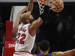 Bulls forward Taj Gibson dunks over Knicks guards Landry Fields and Baron Davis during their game on Tuesday night.
