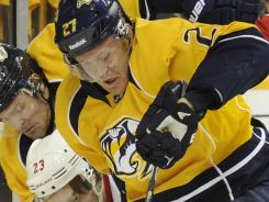 Nashville Predators right wing Patric Hornqvist (27) and center Mike Fisher (12) battle Detroit Red Wings defenseman Brad Stuart (23) for the puck during the first period.
