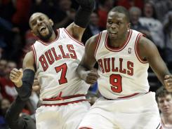 C.J. Watson (7) celebrates his game-tying three-pointer in the closing seconds of regulation with Luol Deng (9).