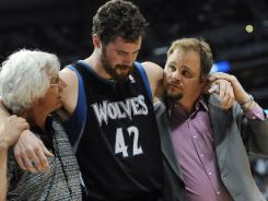 Minnesota Timberwolves All-Star forward Kevin Love is helped off the floor after sustaining a concussion in Wednesday's loss at the Denver Nuggets.