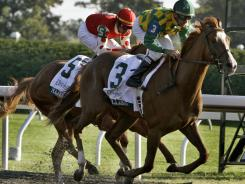 Dullahan, right, under jockey Kent Desormeaux, ran past Majestic City and jockey Garrett Gomez to win the Breeders' Futurity at Keeneland Race Course.