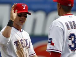 The Texas Rangers' Michael Young, left, and Mike Adams congratulate each other following the win over Seattle.