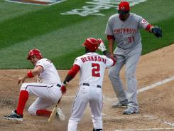 Nationals' Ryan Zimmerman, left, scores the game winning run on a wild pitch by pitcher Reds' Alfredo Simon.