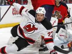 The Devils' David Clarkson is checked by the Panthers' Erik Gudbranson during the second period.