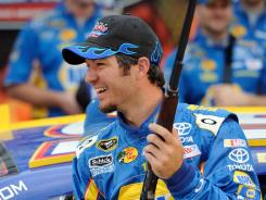 Martin Truex Jr., who captured his first pole position since last fall at Dover, holds a Tumbull rifle in victory lane Friday at Texas Motor Speedway.
