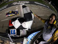 Greg Biffle, driver of the No. 16 Ford, takes the checkered flag to win the NASCAR Sprint Cup Series Samsung Mobile 500 at Texas Motor Speedway on Saturday.