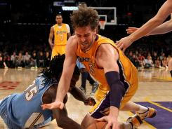 Los Angeles' Pau Gasol dives for a loose ball against Denver's Kenneth Faried in the Lakers' win over the Nuggets on Friday at Los Angeles.