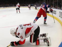 Ottawa's Daniel Alfredsson lies on the ice after an elbow from New York's Carl Hagelin Saturday.