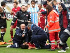 Medics treat Livorno midfielder Piermario Morosini after he collapsed during an Italian federation game against Pescara on Saturday.