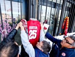 Fans hang Piermario Morosini's jersey outside Livorno's Armando Picchi stadium Sunday, a day after the midfielder died of cardiac arrest.
