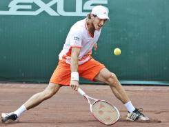 Juan Monaco chops a return during his three-set victory Sunday against John Isner in the final of the U.S. Clay Court Championship in Houston.