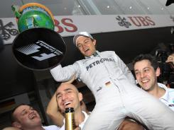 Mercedes Formula One driver Nico Rosberg of Germany is held aloft by his teammates as they celebrate his win at the Chinese Grand Prix in Shanghai on Sunday.