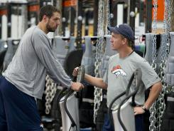 Peyton Manning, right, and Jacob Tamme, both formerly of the Colts, talk during workouts Monday.