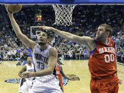 Magic forward Ryan Anderson, left, scoring on a reverse layup past the 76ers' Spencer Hawes, tallied 26 points and 16 rebounds to lead Orlando.