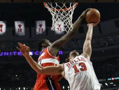 Wizards forward Kevin Seraphin, left, blocks the shot of Bulls center Joakim Noah during the first half of their game. Seraphin finished with 21 points and 13 rebounds.