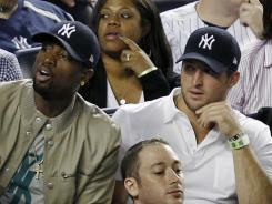 The Miami Heat's Dwayne Wade, left, sits beside New York Jets quarterback Tim Tebow during the New York Yankees baseball game against the Los Angeles Angels at Yankee Stadium in New York on Sunday.
