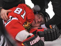 Chicago Blackhawks right wing Marian Hossa lies on the ice after he was hit by Raffi Torres. He left on a stretcher.