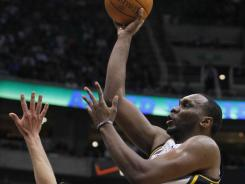 Jazz center Al Jefferson, right, goes up over the Mavericks' Dirk Nowitzki for two of his 28 points. Jefferson added 26 rebounds in Utah's triple-overtime victory.
