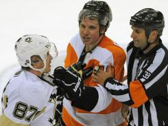 Philadelphia's Brayden Schenn and Pittsburgh's Sidney Crosby are separated by referee Kevin Pollock during the third period Sunday.