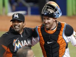 Miami Marlins manager Ozzie Guillen celebrates with catcher John Buck after the Marlins beat the Cubs on Tuesday. It was Guillen's first game since being suspended five games for comments about Fidel Castro.