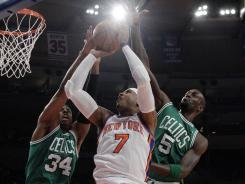 Boston's Paul Pierce (34) and Kevin Garnett (5) defend New York's Carmelo Anthony during the first half of the Knicks' win against the Celtics.