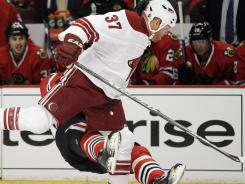 Chicago's Marian Hossa falls after taking a hit from Phoenix's Raffi Torres on Tuesday.