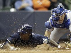 Nyjer Morgan, left, slides safely across home plate with the winning run.
